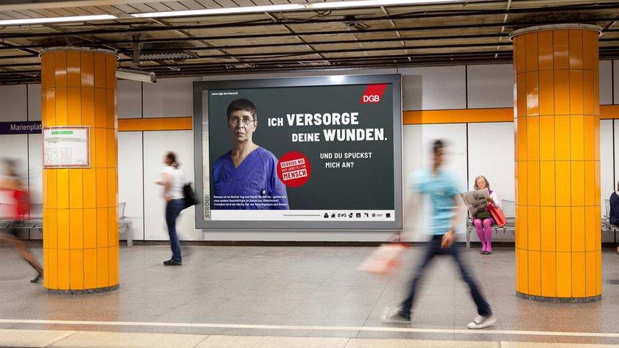 """Plakat an einer Wand im U-Bahnhof mit einer Notfallsanitäterin und der Aufschrift """"Ich versorge deine Wunden. Warum spuckst du mich an?"""""""