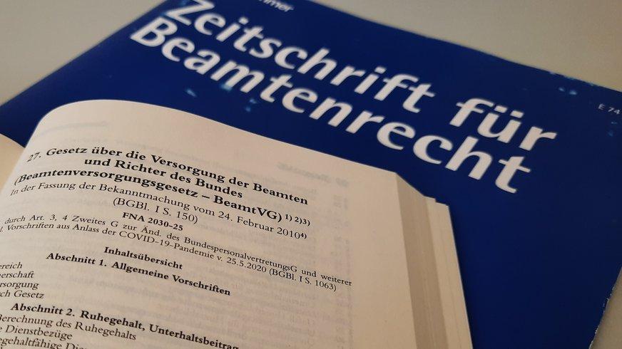 Aufgeschlagener Gesetzestext und Zeitschrift für Beamtenrecht im Hintergrund