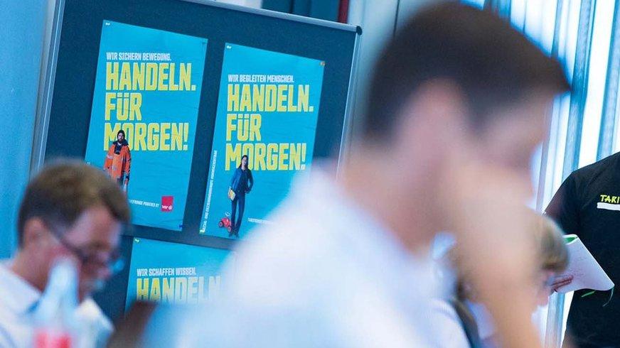 ver.di- Plakate mit Aufschrift Handeln für morgen und im Vordergrund Silhouetten von Personen